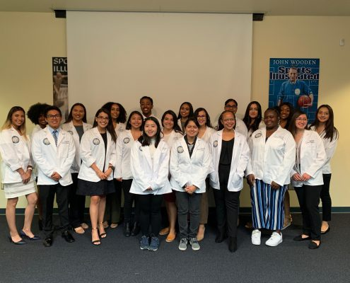 An image of the High Aims Cohort as a group indoors wearing their white coats.